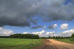 Camino de tierra y nube tormentosa Foto de archivo libre de regalías