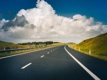 Camino del coche debajo del cielo solar hermoso Imagen de archivo libre de regalías