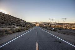 Camino del desierto con algunas antenas grandes de la línea eléctrica Fotografía de archivo