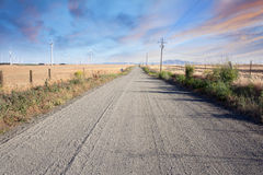 Camino del desierto a través de la granja de las turbinas de viento en las colinas de California Imágenes de archivo libres de regalías