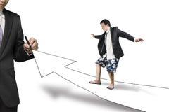Camino del dibujo del hombre de negocios con la flecha del crecimiento la otra remolque que practica surf Fotografía de archivo
