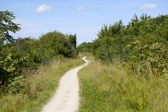 Camino del enrollamiento bajo un cielo nublado azul Fotografía de archivo
