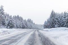 Camino del invierno con el hielo en el asfalto, árboles debajo de la nieve durante la helada del invierno Foto de archivo