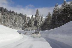 Camino del invierno con los coches en bosque nevoso imagen de archivo