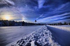 Camino del invierno en el camino del invierno del bosque en el bosque y una señal de tráfico Foto de archivo