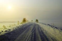 Camino del invierno en el medio del campo Salida del sol en el invierno W foto de archivo