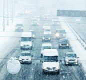 Camino del invierno Nevado con la conducción de automóviles en el camino en tormenta de la nieve Imagenes de archivo