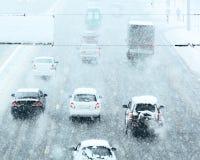 Camino del invierno Nevado con la conducción de automóviles en el camino en tormenta de la nieve Imagen de archivo