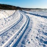 Camino del invierno Nevado con las marcas del neumático Fotos de archivo libres de regalías
