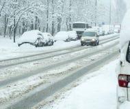 Camino del invierno Nevado con los coches en tormenta de la nieve Imagen de archivo libre de regalías