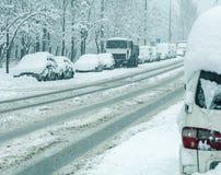 Camino del invierno Nevado con los coches en tormenta de la nieve Foto de archivo libre de regalías
