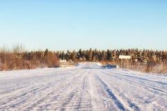 Camino del invierno a través de campos y de bosques nevosos Foto de archivo libre de regalías
