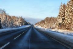 Camino del invierno a través de campos y de bosques nevosos Fotos de archivo libres de regalías