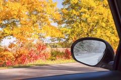 Camino del otoño con los árboles brillantes coloridos y un espejo de coche con reflexiones del camino del invierno imagenes de archivo