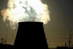 Camino della centrale elettrica contro il sole Immagini Stock