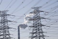 Camino di fumo e righe elettriche ad alta tensione Immagine Stock