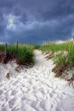 Camino en duna de arena bajo el cielo tempestuoso Foto de archivo