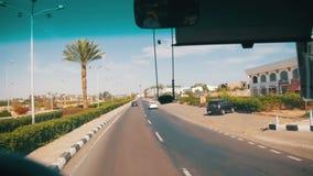 Camino en Egipto La visión desde el autobús de visita turístico de excursión va en el camino cerca de las palmas y de los hoteles metrajes