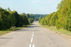 Camino en el bosque con un camión en la distancia Fotografía de archivo libre de regalías