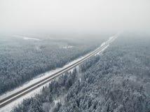 Camino en el bosque congelado del invierno con la conducción de los coches Perspectiva de desaparición de niebla del punto aéreo Imagen de archivo libre de regalías