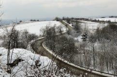 Camino en invierno con las curvas vistas de distancia Fotografía de archivo libre de regalías