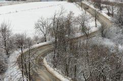 Camino en invierno con las curvas vistas de distancia Foto de archivo