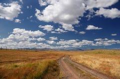 Camino en una meseta salvaje de la montaña con la hierba anaranjada en el fondo de las colinas debajo de un cielo azul Foto de archivo