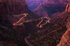 Camino en Zion National Park con los rastros de la luz del coche imagenes de archivo