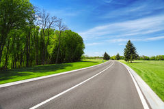 Camino entre los árboles y la hierba en el borde de la carretera Imagen de archivo libre de regalías