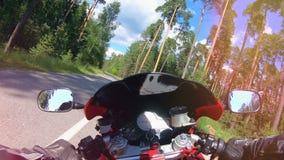 Camino forestal con una moto que se mueve en una visión de primera persona POV Montar a caballo del motorista abajo de la carrete metrajes