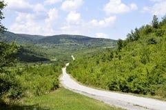 Camino a la montaña en rural con el cielo azul Fotos de archivo libres de regalías