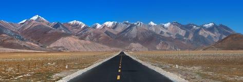 Camino largo a continuación con la alta montaña en frente Fotografía de archivo libre de regalías