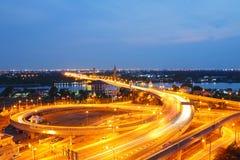 Camino largo de la luz de la exposición en la autopista con el puente de Nonthaburi Mahajetsadabadin en la puesta del sol foto de archivo