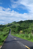 Camino local, colina verde y opinión de cielo azul Fotografía de archivo