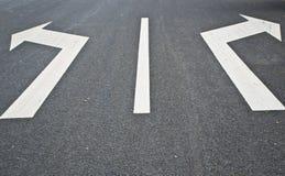Camino marca-con dos flechas que señalan en direcciones opuestas Foto de archivo libre de regalías