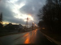 Camino mojado, oscuro con la luz Foto de archivo