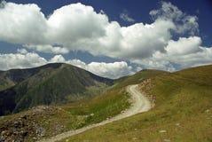 Camino, montañas y nubes Imagen de archivo libre de regalías