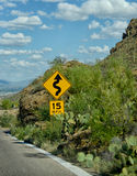Camino 15 mph de la advertencia de la muestra de curvas en el camino a continuación imagenes de archivo