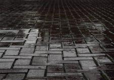 Camino negro mojado del ladrillo después de la precipitación pesada Imagen de archivo libre de regalías