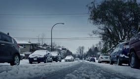 Camino nevado con los coches que pasan en invierno metrajes