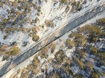Camino nevado con un coche móvil en invierno Imagen de archivo libre de regalías