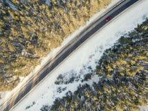 Camino nevado con un coche móvil en invierno Foto de archivo