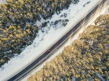 Camino nevado con un coche móvil en invierno Fotos de archivo