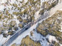 Camino nevado con un coche móvil en invierno Fotografía de archivo libre de regalías