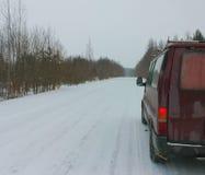 Camino nevado y la furgoneta roja en el borde de la carretera Imagen de archivo