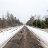 Camino nevoso del país en invierno Imagen de archivo libre de regalías