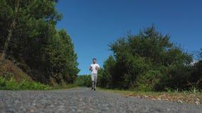 Camino que activa del hombre joven en el bosque almacen de metraje de vídeo
