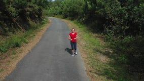 Camino que activa en el bosque, vídeo de la mujer joven de la cámara lenta almacen de video