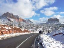 Camino que corre a través de las motas rojas nevadas de Arizona Fotografía de archivo libre de regalías