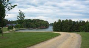 Camino que curva alrededor al lago y al granero Foto de archivo libre de regalías